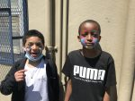 """two children with brown and dark brown skin with colorful make up on their cheeks one is wearing a white t-shirt with a black jacket and the other is wearing a black t-shirt with the word """"PUMA"""" on the chest"""